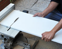 Der Tischler, der ein Brett des weißen Melamins mit Scheibenenergie schneidet, sah Stockfotos