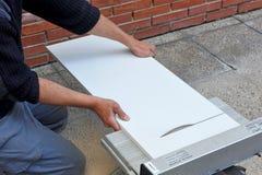 Der Tischler, der ein Brett des weißen Melamins mit Scheibenenergie schneidet, sah Lizenzfreie Stockfotos