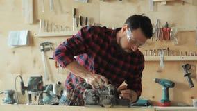 Der Tischler planiert das Holz stock footage