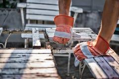 Der Tischler repariert die Tabelle Durch das Tragen von Handschuhen zum preve Lizenzfreie Stockfotos