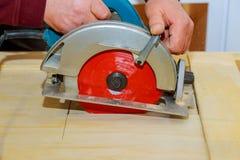 Der Tischler, der Rundschreiben verwendet, sah den Schnitt von hölzernen Brettern mit Elektrowerkzeugen Lizenzfreie Stockbilder