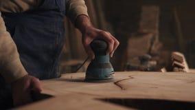Der Tischler in seiner kleinen Werkstatt arbeitet an dem Polieren des Stück Holzes sandpapierschleifmaschine Zielen des Schießens stock footage