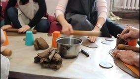 In der Tonwarenwerkstatt bereiten Leute Tonwaren vor Handnahaufnahme, heller Hintergrund Handarbeitkonzept stock footage