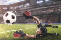 Der Torhüter springend für den Ball auf Fußballspiel lizenzfreie stockfotografie