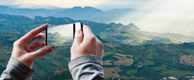 Der Tourist, der ein Foto von Sun macht, strahlt das Glänzen unten auf Hügeln aus Stockfotos
