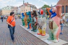 Der Tourist, der die bunten Bären auf die internationale Kunstausstellung vereinigter Buddy Bears betrachtet Der Bärnkreis war stockfotografie