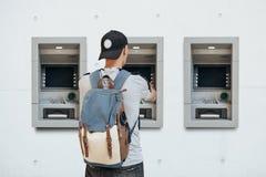Der Tourist nimmt Geld vom ATM für weitere Reise zurück lizenzfreies stockbild