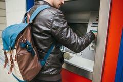 Der Tourist nimmt Geld vom ATM für weitere Reise zurück Ergreift eine Karte vom ATM Finanzierung, Kreditkarte, Zurücknahme Lizenzfreies Stockfoto
