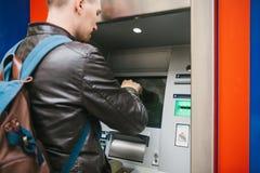 Der Tourist nimmt Geld vom ATM für weitere Reise zurück Finanzierung, Kreditkarte, Abhebung von Geld reise Stockfoto