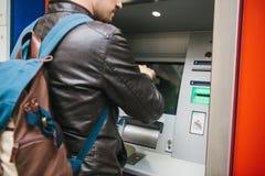 Der Tourist nimmt Geld vom ATM für weitere Reise zurück Finanzierung, Kreditkarte, Abhebung von Geld reise Stockfotografie