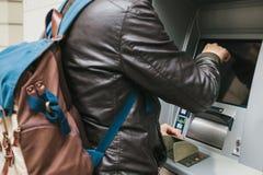 Der Tourist nimmt Geld vom ATM für weitere Reise zurück Finanzierung, Kreditkarte, Abhebung von Geld reise Stockbilder