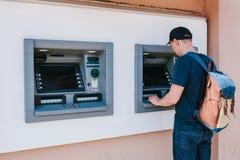 Der Tourist nimmt Geld vom ATM für weitere Reise zurück Finanzierung, Kreditkarte, Abhebung von Geld Sehen Sie meine anderen Arbe Stockbild