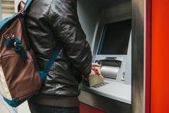Der Tourist nimmt Geld vom ATM für weitere Reise zurück Wählt den Code mit einer Hand und schließt die Knöpfe mit Stockfoto