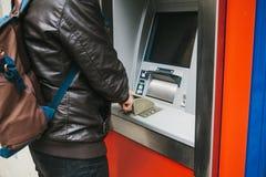 Der Tourist nimmt Geld vom ATM für weitere Reise zurück Wählt den Code mit einer Hand und schließt die Knöpfe mit Stockfotografie