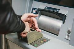Der Tourist nimmt Geld vom ATM für weitere Reise zurück Wählt den Code mit einer Hand und schließt die Knöpfe mit Lizenzfreies Stockfoto