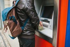 Der Tourist nimmt Geld vom ATM für weitere Reise zurück Wählt den Code mit einer Hand und schließt die Knöpfe mit Stockbild