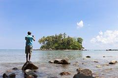 Der touristische Mann, der auf dem Stein in der Sommersaison steht und nehmen einen pH Lizenzfreie Stockfotos