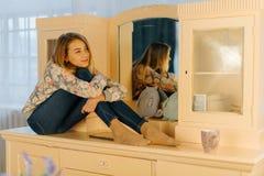 Der träumende blonde Jugendliche umarmt die Knie beim Sitzen auf dem Aufbereiter Die Seitenansicht Lizenzfreie Stockbilder