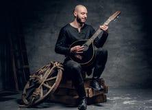 Der traditionelle Volksmusiker, der in der keltischen Kleidung der Weinlese gekleidet wird, sitzt auf einer Holzkiste und spielt  lizenzfreies stockfoto