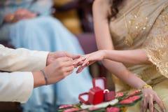 Der tragende Ehering des Bräutigams für seine Braut Lizenzfreies Stockfoto