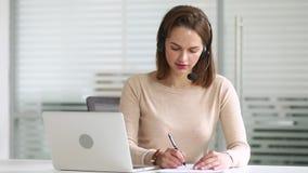 Der tragende Kopfhörer der Geschäftsfrau-Empfangsdame, der Laptop betrachtet, machen Anmerkungen stock video footage
