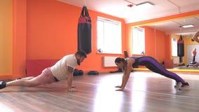 Der Trainer steuert die Übung des Mädchens und des dicken Mannes auf Geschwindigkeit und Reaktion, Aufwärmen, einzelner Trainer stock video