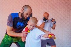 Der Trainer unterrichtet das Jungenkickboxen stockbild