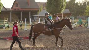 Der Trainer unterrichtet das Kind, zu Pferd zu sitzen