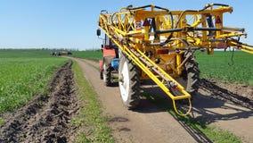 der Traktor auf der Straße unter Feldern des grünen Weizens Lizenzfreie Stockfotos