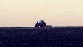 Der Traktor, der das Feld kultiviert stock video