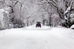 Der Traktor, der hinunter einen Schnee antreibt, deckte Straße ab Stockfotografie