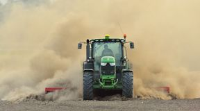 Der Traktor eggt das Feld in einer enormen Staubwolke Lizenzfreies Stockfoto