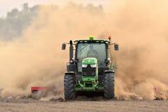 Der Traktor eggt das Feld in einer enormen Staubwolke Lizenzfreie Stockfotos