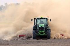 Der Traktor eggt das Feld in einer enormen Staubwolke Lizenzfreies Stockbild