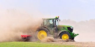 Der Traktor eggt das Feld in einer enormen Staubwolke Stockbild