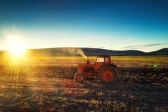 Der Traktor, der Feld am Frühling, Sonnensätze kultiviert, dämmern behint die Hügel lizenzfreie stockfotografie