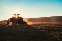 Der Traktor, der Feld am Frühling, Sonnensätze kultiviert, dämmern behint die Hügel stockfoto