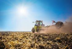 Der Traktor pflügt das Feld, kultiviert den Boden für Saatgetreide Das Konzept der Landwirtschaft lizenzfreie stockfotos