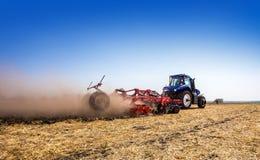 Der Traktor pflügt das Feld, kultiviert den Boden für Saatgetreide Das Konzept der Landwirtschaft stockbild