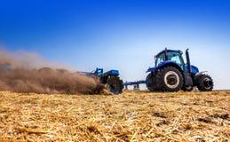 Der Traktor pflügt das Feld, kultiviert den Boden für Saatgetreide Das Konzept der Landwirtschaft stockbilder
