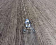 Der Traktor pflügt das Feld Unter Säen wird der Boden auf dem Feld gelöst Lizenzfreie Stockbilder