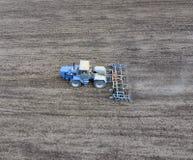Der Traktor pflügt das Feld Unter Säen wird der Boden auf dem Feld gelöst Stockfotografie