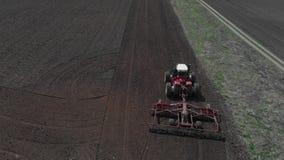 Der Traktor pfl?gt den Boden auf dem Feld zu Beginn der pflanzenden Jahreszeit Ein Landwirt steht auf den Bahnen von seinem stock video footage