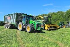 Der Traktor Rad John Deeres 8335R mit dem Anhänger und dem Futter, die Mähdrescher John Deeres 7450 ernten Lizenzfreie Stockfotos