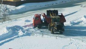 Der Traktor, der Schnee in den LKW entleert stock footage
