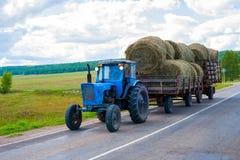 Der Traktor trägt Ballen Heu Stockbild