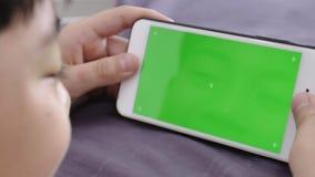 Der Transportwagen, der vom Kind geschossen wird, hält ein Telefon in seiner Hand mit einem grünen Schirm für Farbenreinheitsschl stock video