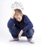 Der traurige jugendliche Junge, der auf dem Boden sitzt, lokalisierte ein weißes backgro Lizenzfreies Stockbild