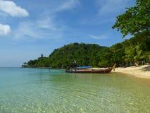 Der tropische Strand mit einem Boot Lizenzfreie Stockbilder
