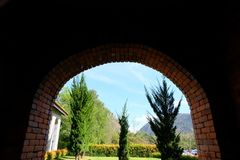 Der Tunnel, der durch Ziegelsteinweisendurchlauf zum Garten hergestellt wird, haben sind Baum- und Grasland Stockfoto